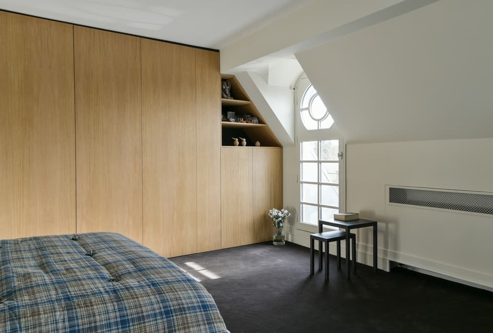 Contemporary bedroom with carpet flooring and white walls. Photo credit: Mickaël Martins Afonso