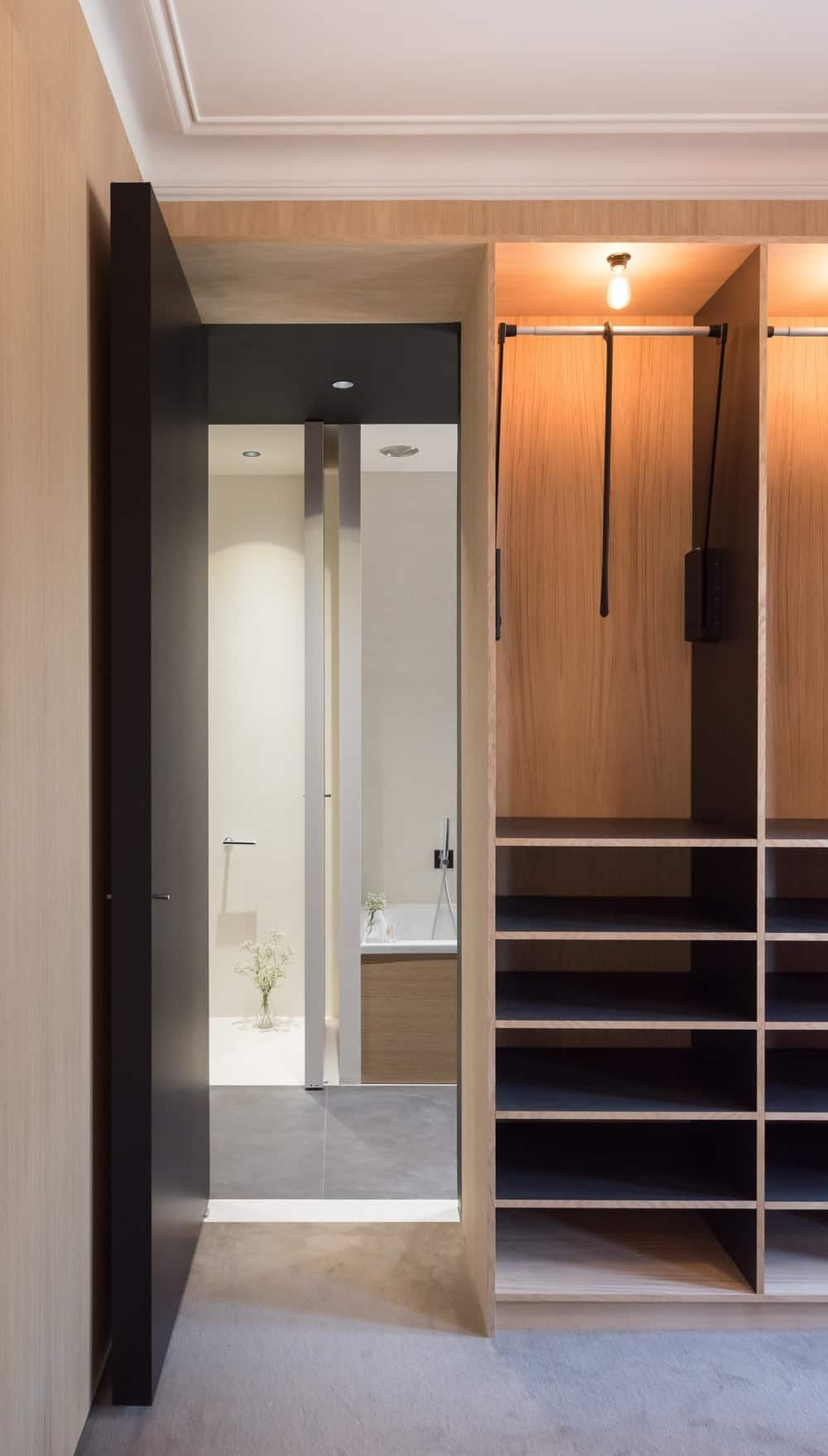 Large closet with large storage cabinet and doorway leading to the bathroom. Photo credit: Mickaël Martins Afonso