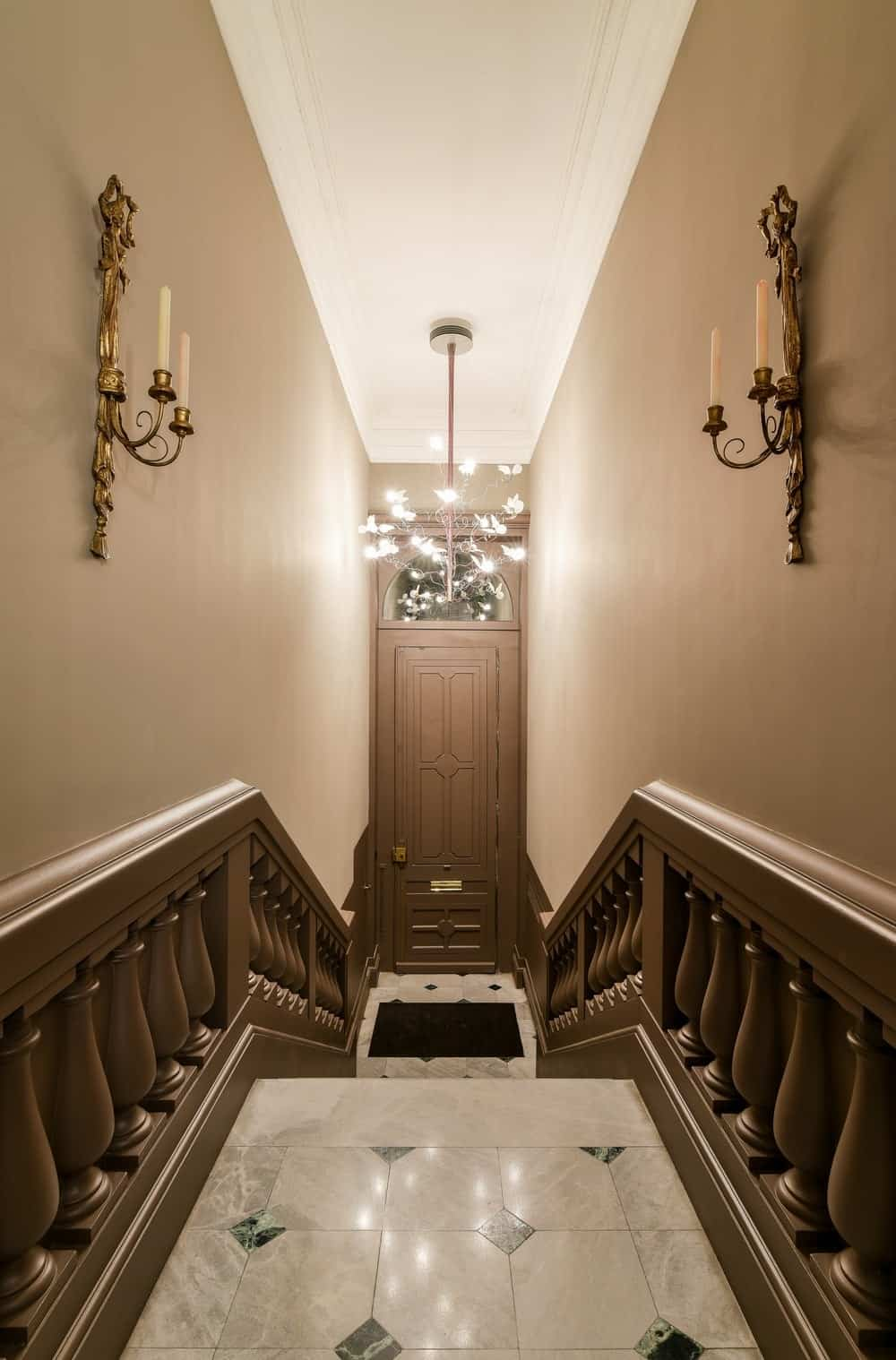 Entry hall with straight staircase lighted by a chandelier and wall lights. Photo credit: Mickaël Martins Afonso