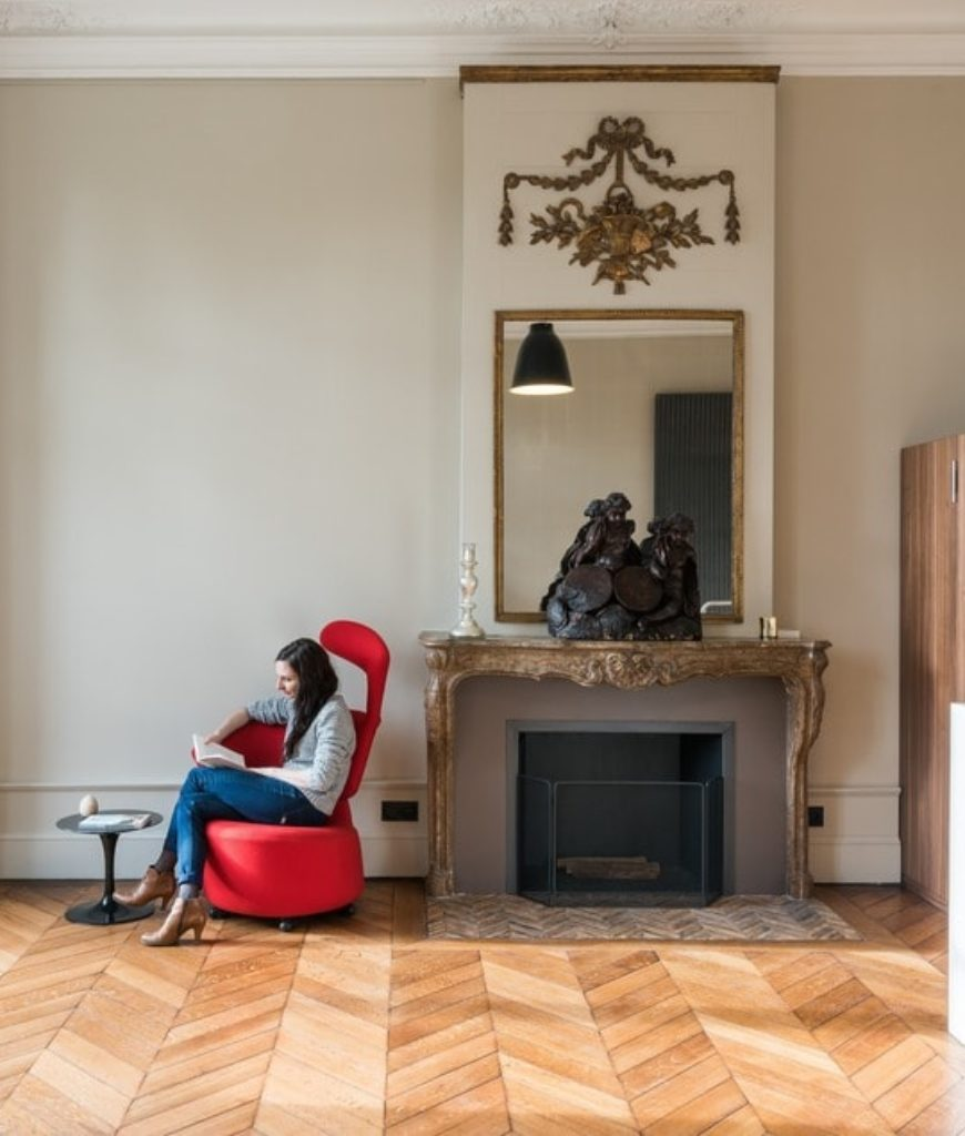 Contemporary seating spot near the kitchen with red chair and small coffee table near the fireplace. Photo credit: Mickaël Martins Afonso