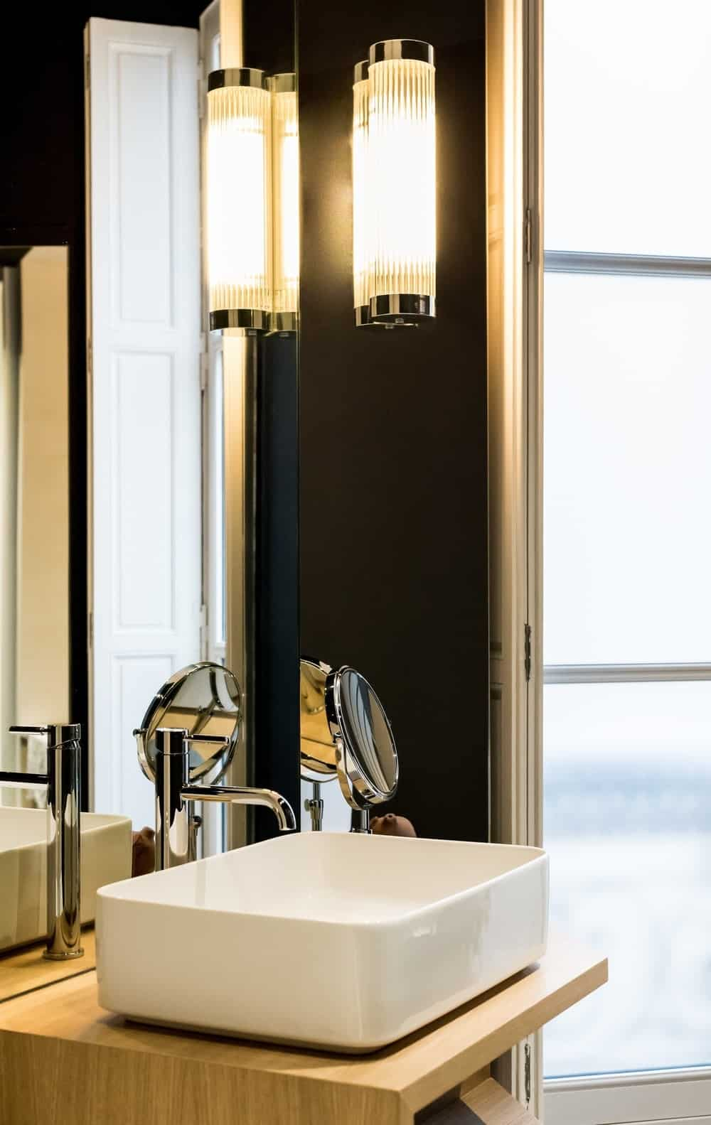 Vessel sink on a contemporary bathroom lighted by a wall light. Photo credit: Mickaël Martins Afonso