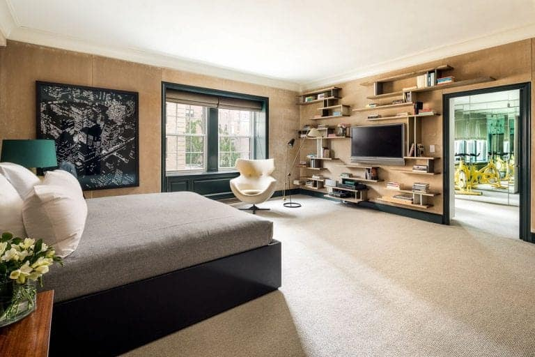 Large master bedroom featuring carpet flooring and brown walls with multiple built-in shelves. There's a chair near the windows. The wall decor looks absolutely stylish.