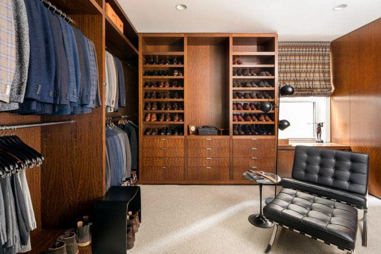 This men's modern closet features brown finished cabinetry and walls. There carpet flooring adds elegance to the room.