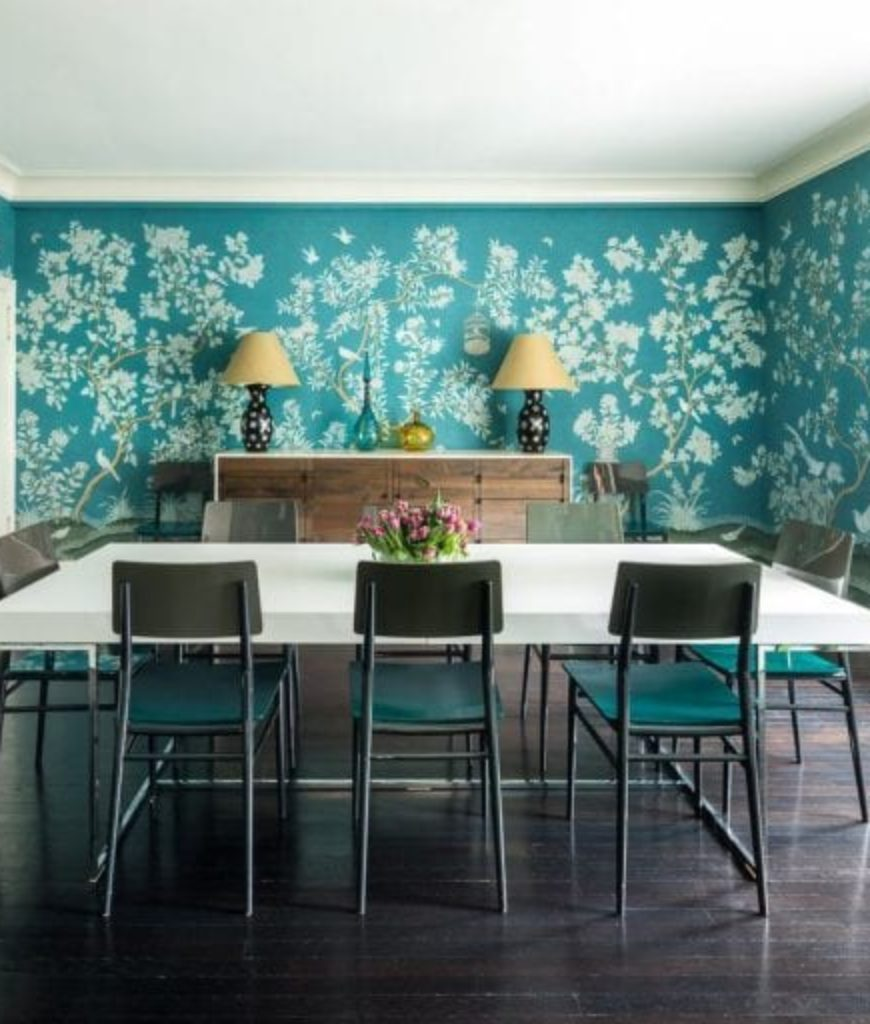Dining area boasts a dark hardwood flooring with a modish table and chairs set surrounded by blue green walls with design.