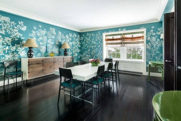 Charming dining room clad with lovely blue green floral wallpaper. It has a natural wood buffet table across a white smooth dining table and black metal chairs.