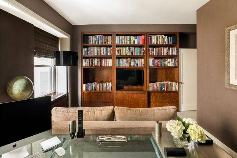 The home also features a family room with a large bookshelf with a wide screen TV. Brown walls looks stylish along with the room's set up.