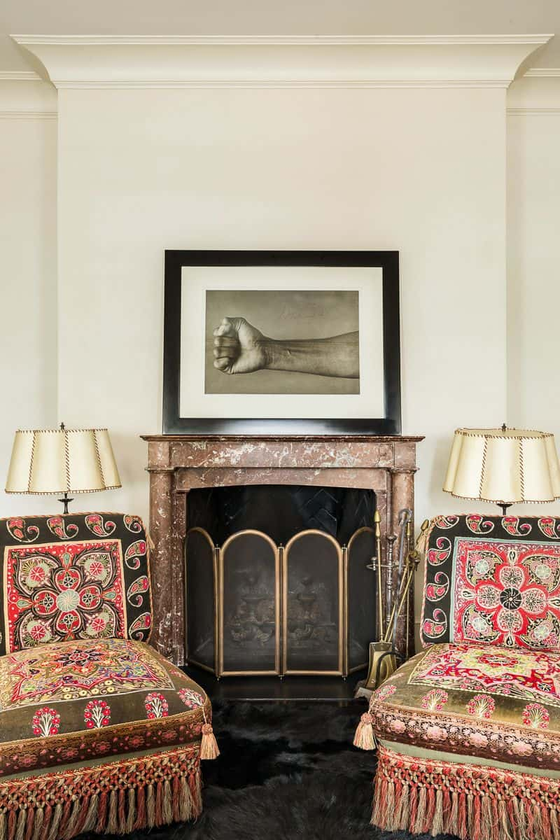 A seating area is placed near the fireplace with a couple of table lamps with a wall decor on top of the fireplace.