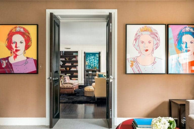 The doorway leading to living spaces features a beige wall decorated by artistic paintings.