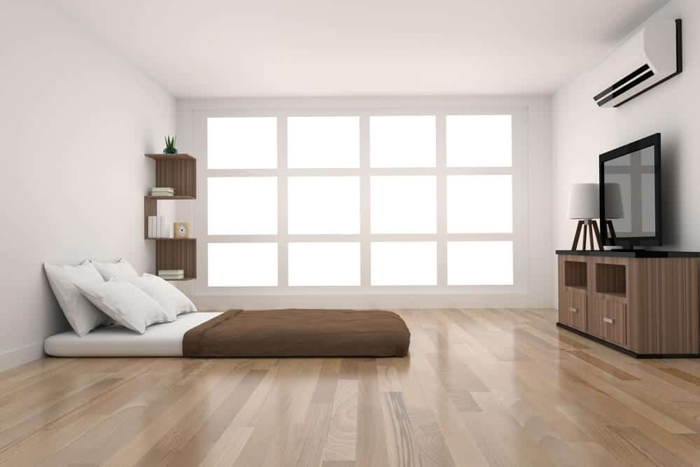 White mattress with a brown blanket on the floor.