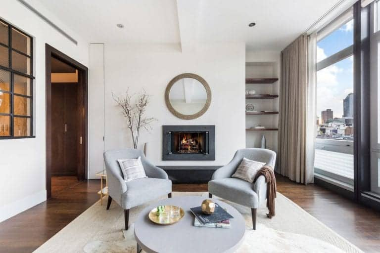 Classy gray armchairs sit in front of the fireplace in this living room with round coffee table and open shelving.