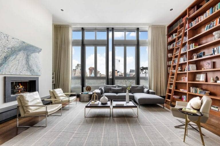 The penthouse's reading room includes a large bookshelf with a ladder just beside the sofa set backed by additional seating spots near the fireplace.