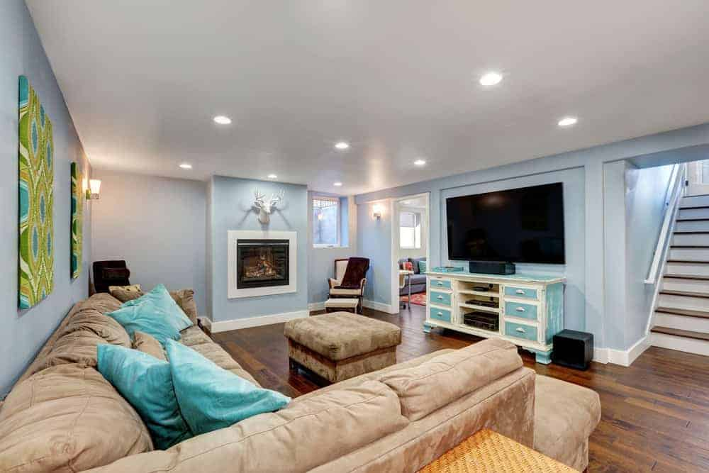 Nicely finished basement with TV, sofa and soft blue walls.