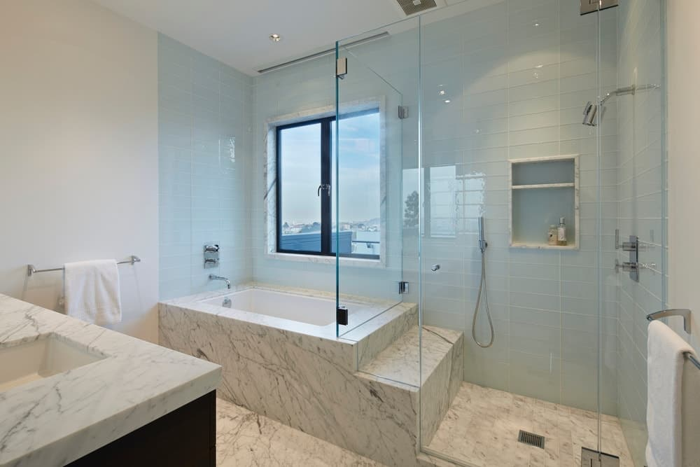 Modern white bathroom with drop-in tub and walk-in shower along with marble countertop and flooring. Photo credit: Bruce Damonte