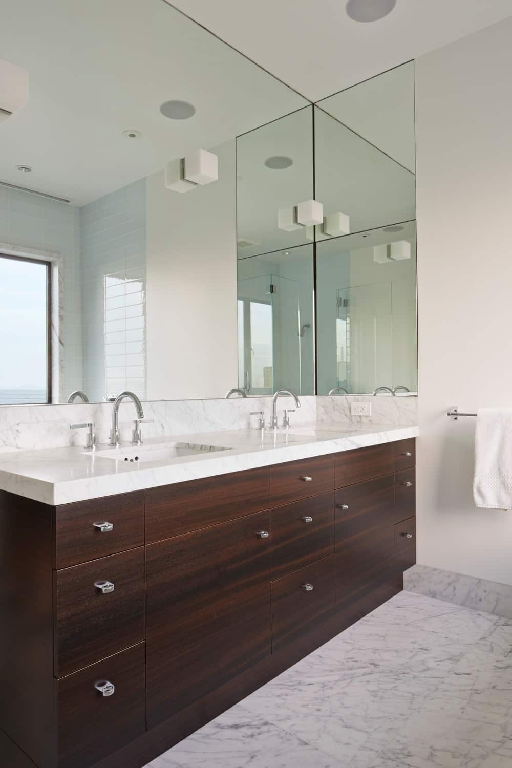 Modern bathroom with double sink featuring marble countertop and wide mirror. Photo credit: Bruce Damonte