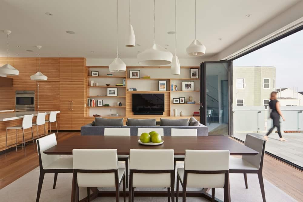 Modern dining area with a stylish rectangular table and chairs set lighted by pendant lights. Photo credit: Bruce Damonte