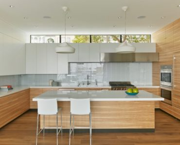 Modern kitchen a large center island featuring smooth countertops and stainless steel appliance. Photo credit: Bruce Damonte
