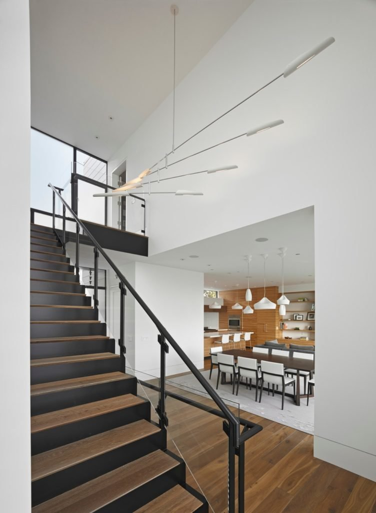 Straight staircase features wooden treads accented with black risers along with glass balustrade that's topped with a black steel handrail. It is illuminated by a white industrial chandelier.