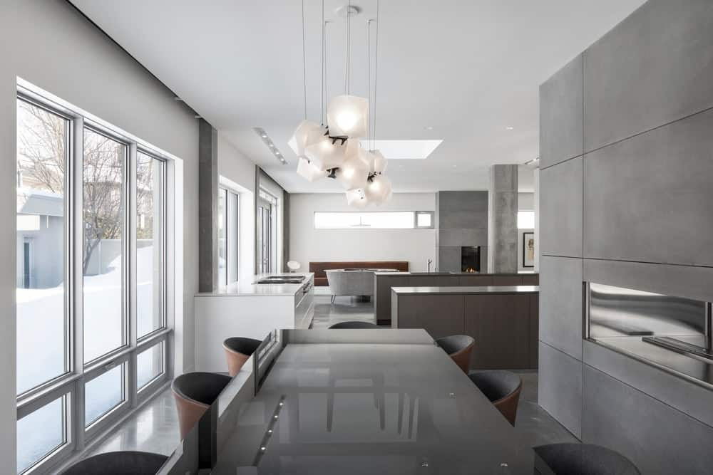 A sleek, modern dining room accented with elegant suspension lamps that hung over a smoked-glass table surrounded by two-tone chairs.