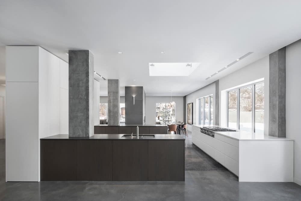 Large kitchen featuring a ceiling with skylight and light gray walls, along with gray flooring.