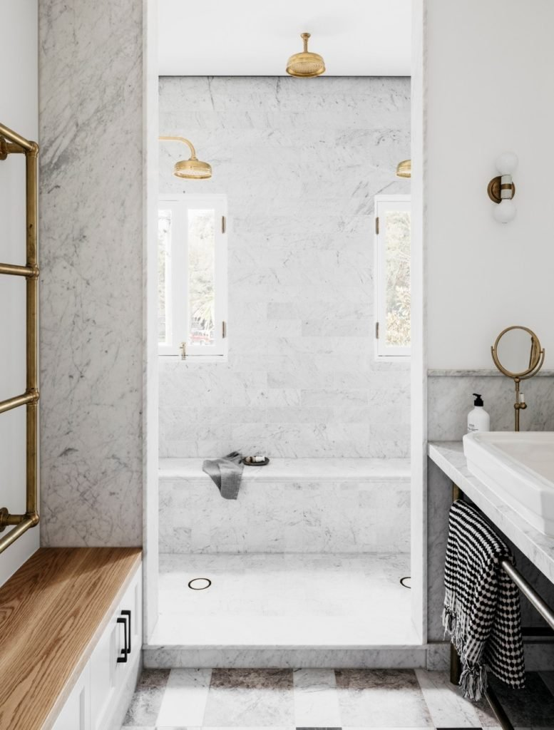 This bathroom boasts a shower room filled with marble floors and walls.