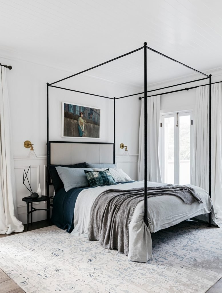 A focused shot at this primary bedroom's stylish bed set on the area rug covering the room's hardwood flooring.