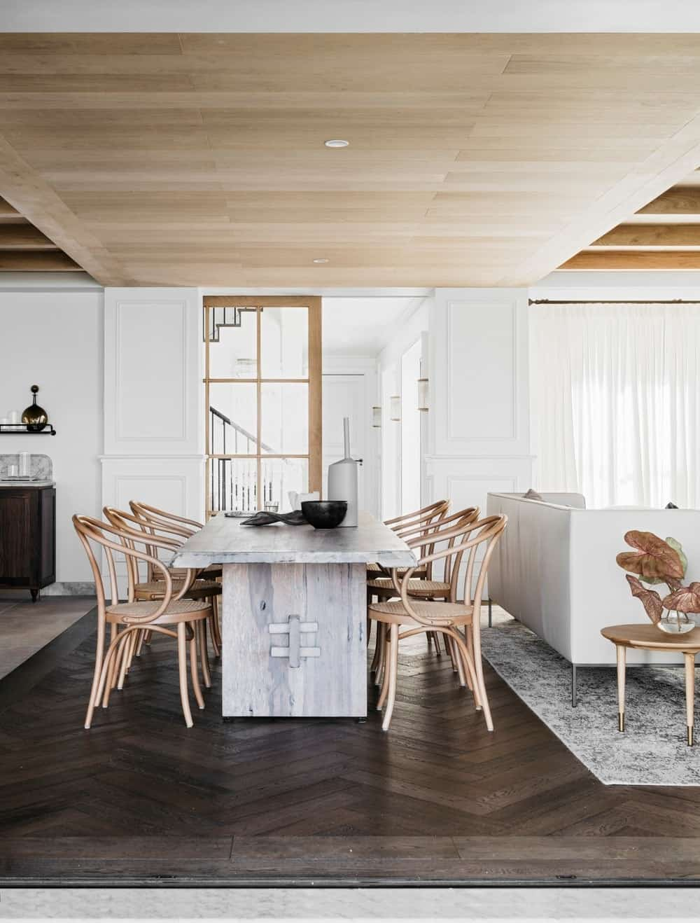 This is an open concept house with a cozy dining space featuring a distressed dining table and wooden round back chairs that can accommodate eight people. A very warming area with wood paneled ceiling and a herringbone flooring.