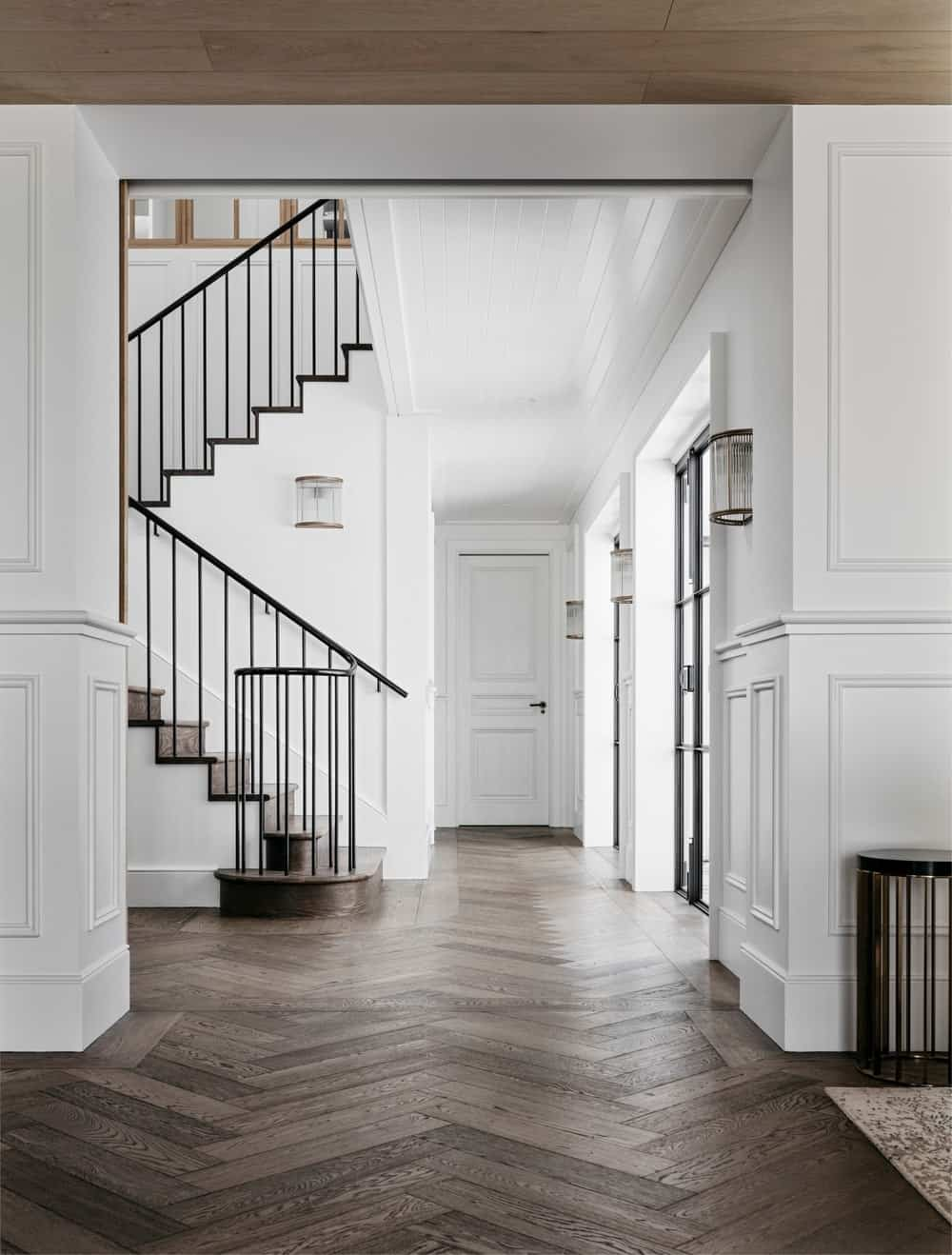 This foyer boasts a hardwood flooring and staircase steps, along with white walls and iron staircase railings.