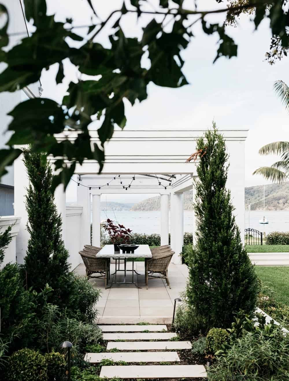 White patio with a beautiful pathway surrounded by trees and green plants leading to the outdoor dining table set.