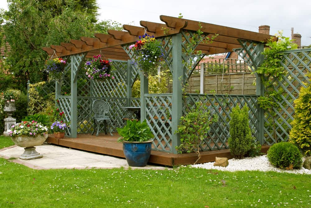 Wooden Pergola In The Backyard With Lattice Half Wall