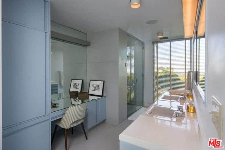 The bathroom has a smooth countertop with warm white wall lighting and a double sink. Built-in desk and a walk-in shower also exist in the room.