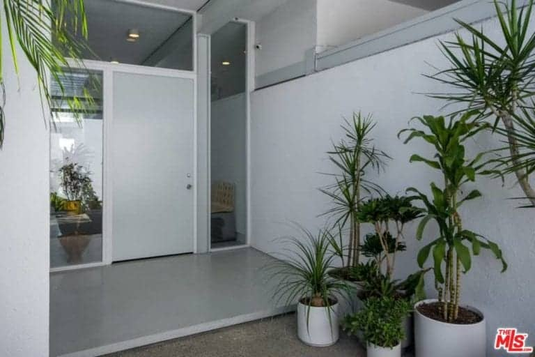 The garden leads to the home's entryway featuring a white door.