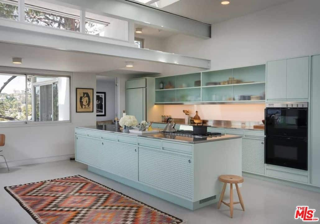 Chic white kitchen with white custom cabinets, white floor, kitchen island, and recessed lights.