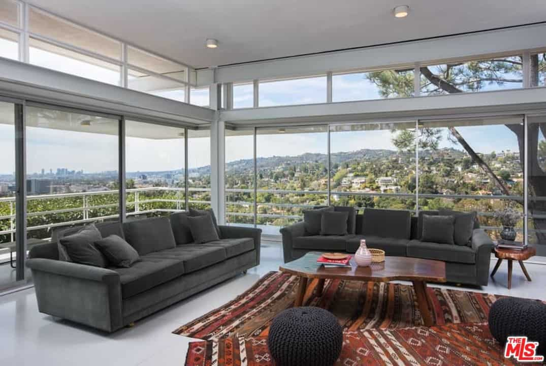 This living room offers a couple of black couches set on a white flooring topped by rug. Glass walls and windows surrounds the place, overlooking the beautiful surroundings outside.