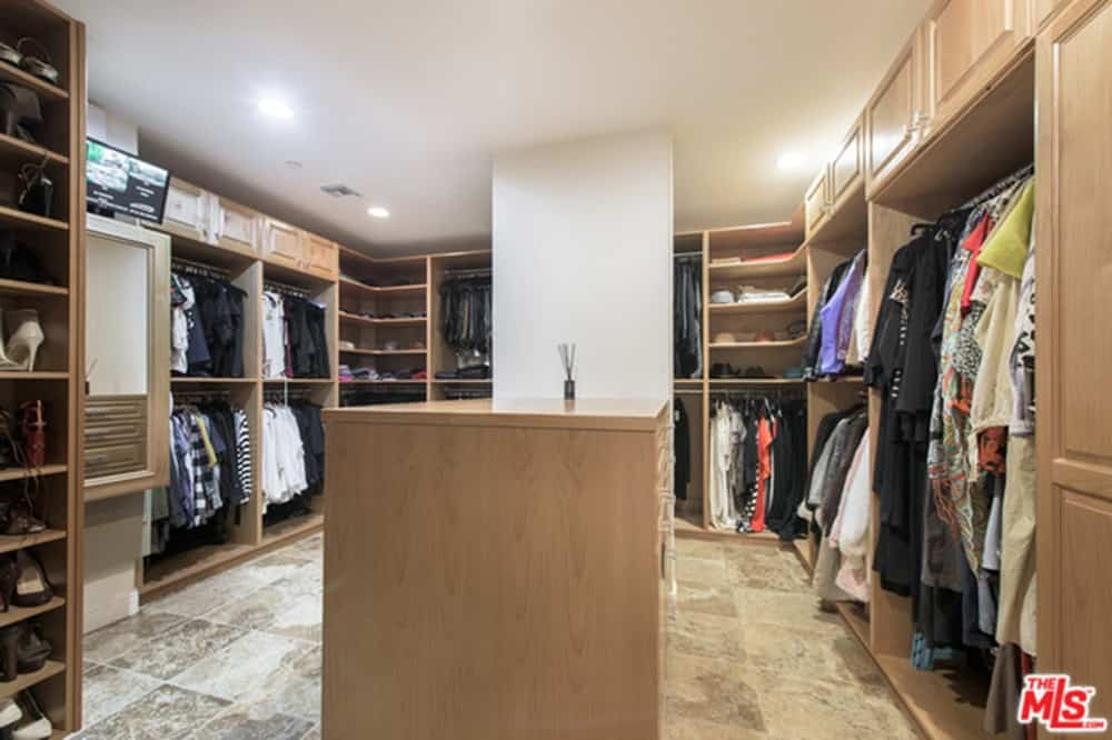 Huge closet provides multiple shelves, storage and clothesline, lighted by recessed ceiling lights.