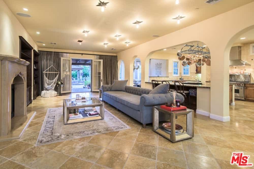 Great room features a fireplace and tiles flooring lighted by beautiful ceiling lights. French door leads to outdoor areas.