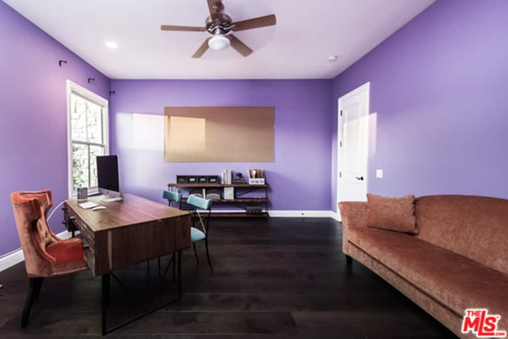 The mansion also boasts a purple home office featuring a brown long sofa and dark hardwood flooring.