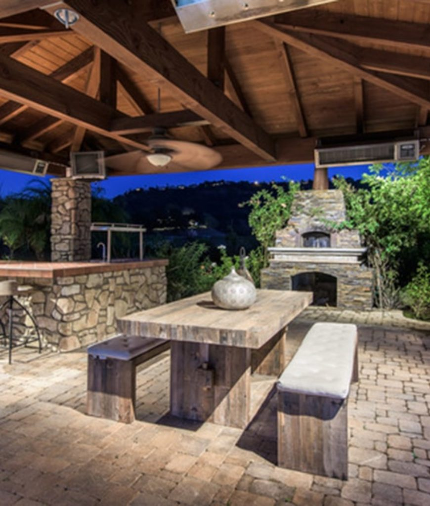 Outdoor kitchen features breakfast bar and a hardwood dining table paired with a couple of bench seating with a fireplace.