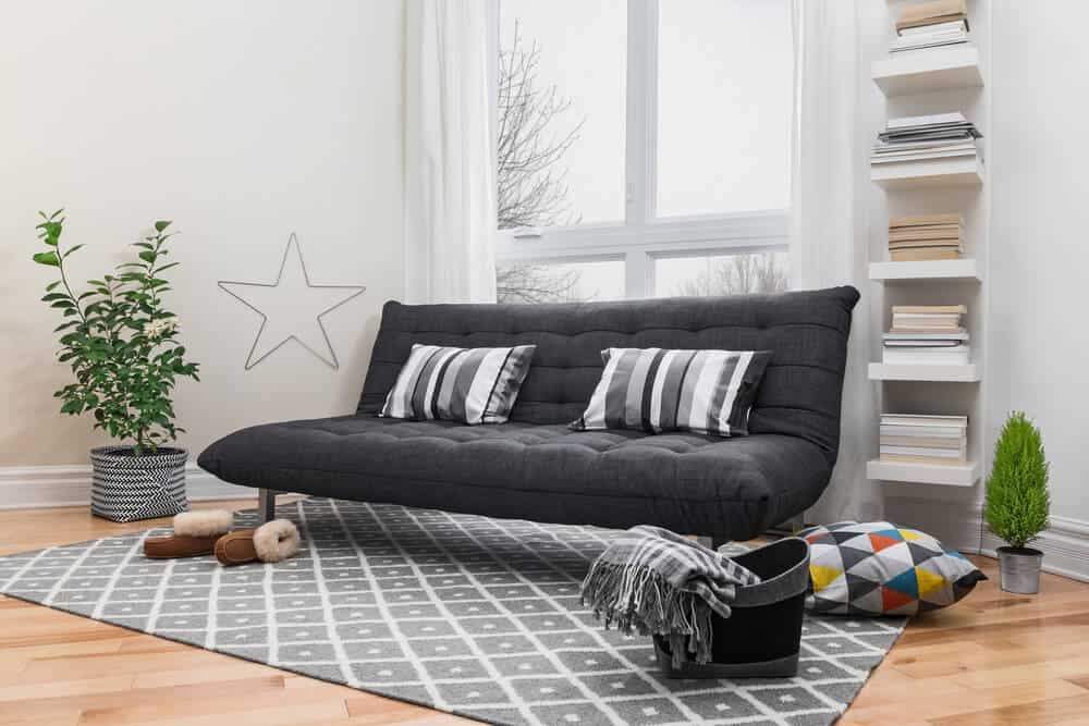Black futon in a minimalistic living room.