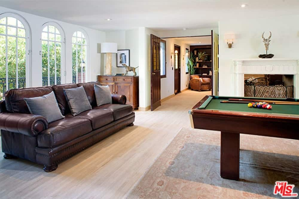The game room features a billard pool and a sofa. Hardwood flooring is topped by a rug.