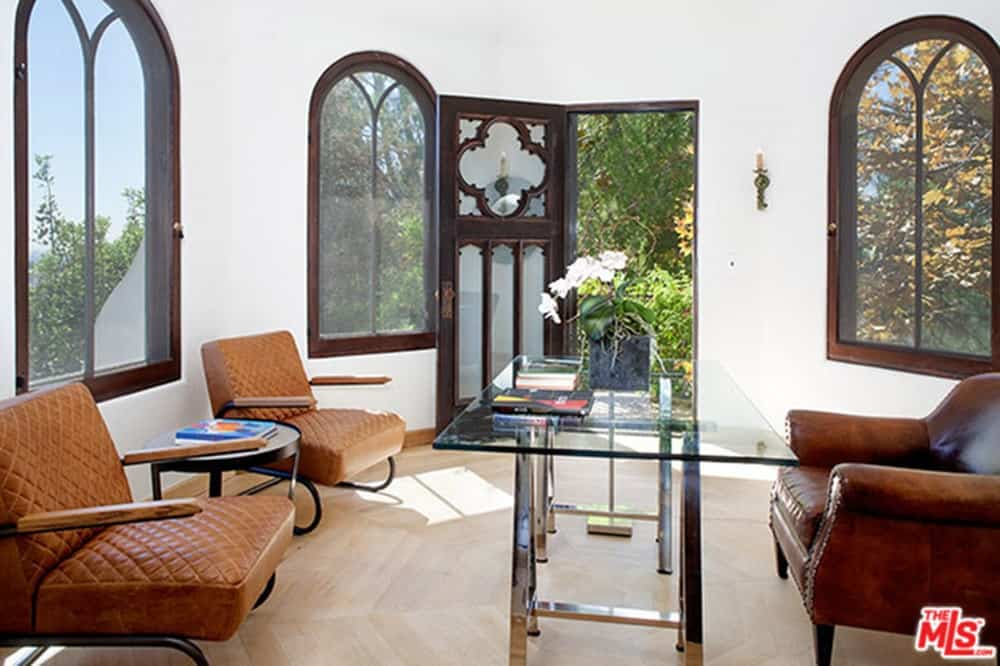 The house also has a home office featuring brown chairs and glass table.