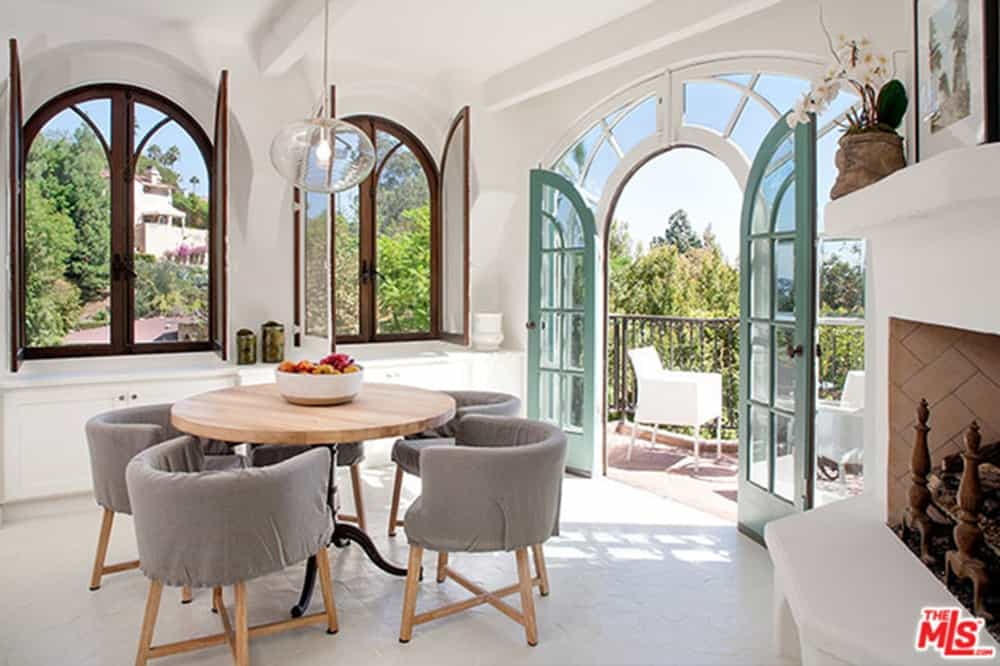 Gray round back dining chairs sit at a wooden round table in this fresh dining room surrounded with arched glass windows and french door.