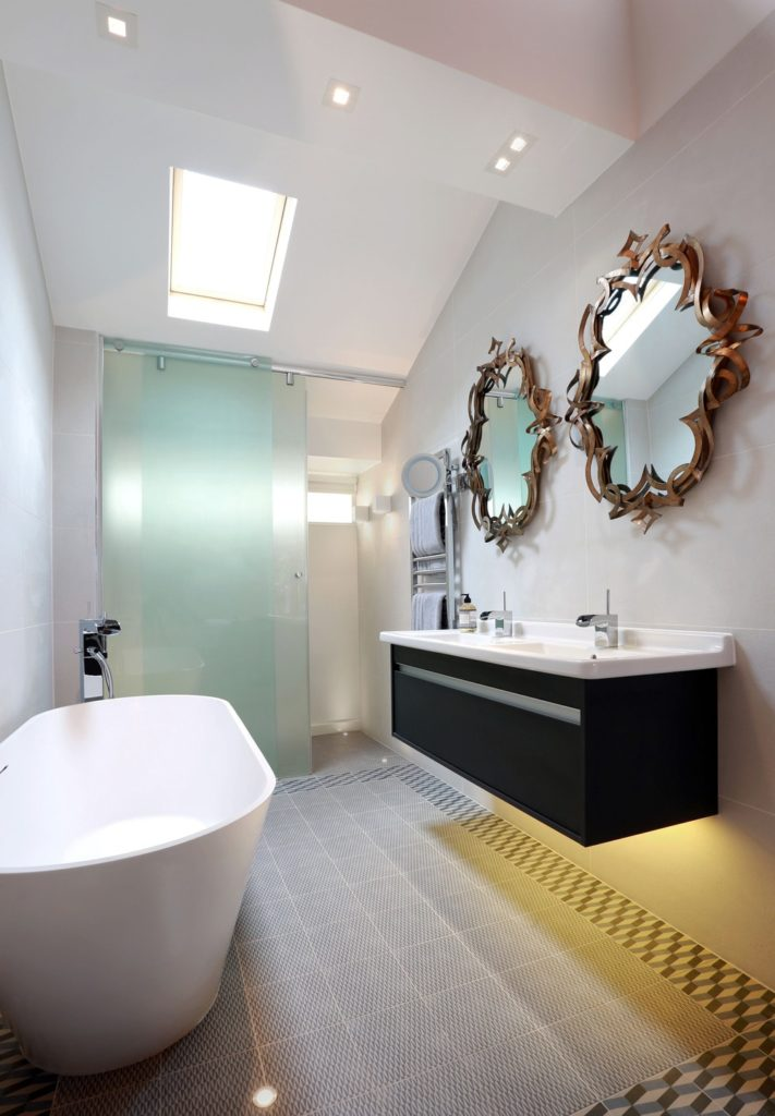Contemporary bathroom inside the primary suite featuring a double sink, a soaking tub and a walk-in shower room.