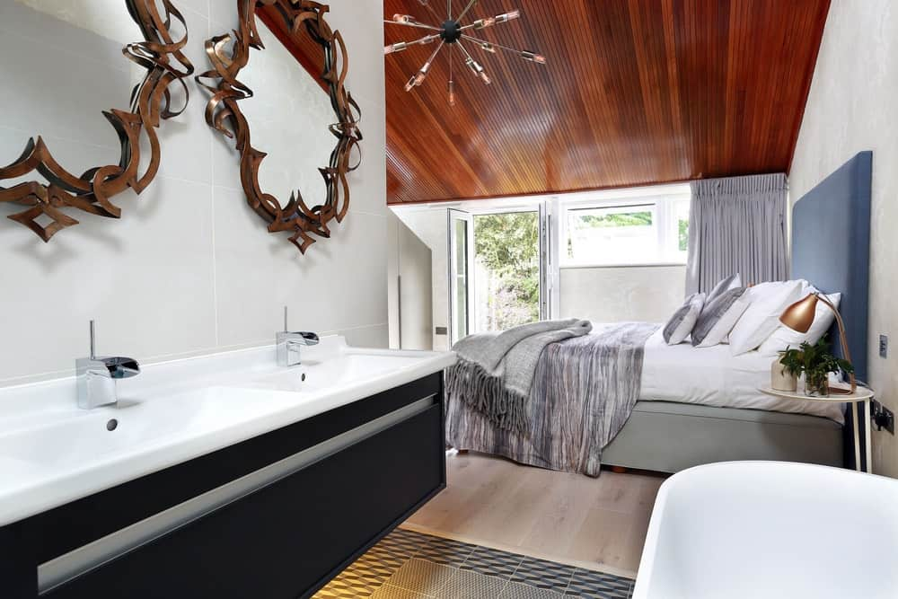 Primary bedroom illuminated by a modern contemporary chandelier. There's an open bathroom beside the bed that features a dual sink vanity and freestanding tub.