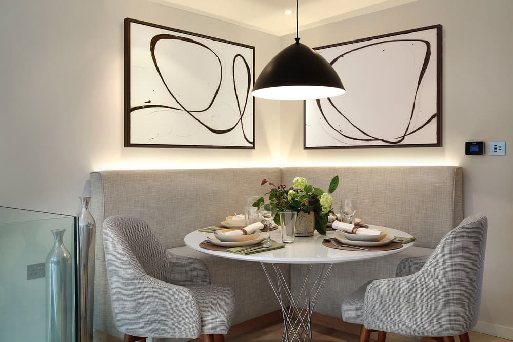 Contemporary dining set with elegant lighting and stylish wall decor. Photo credit: Alex Maguire