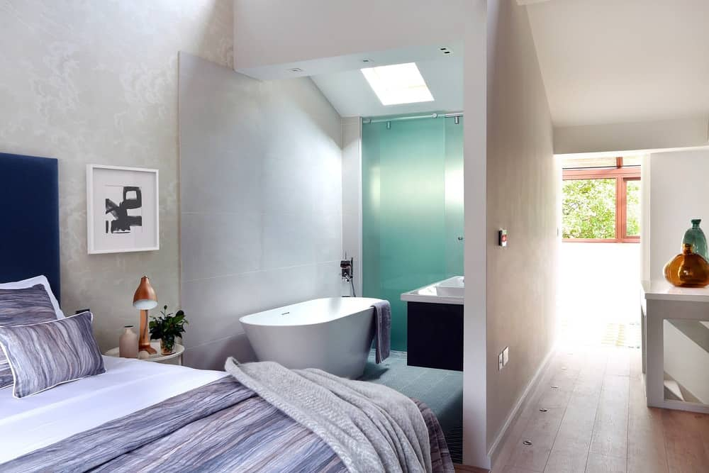 A contemporary primary suite with an open bathroom on its side featuring a freestanding tub and a walk-in shower area.