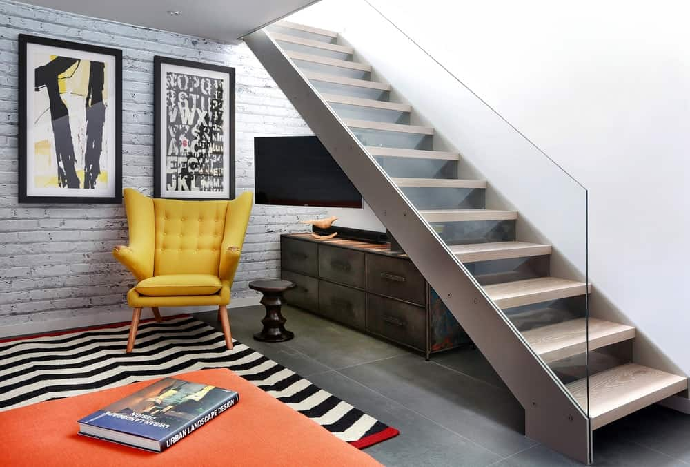 Contemporary staircase fitted with a frameless glass railing and light wood treads. It has a rustic chest drawer underneath it with a yellow tufted chair and round side table over black striped and orange layered rugs.