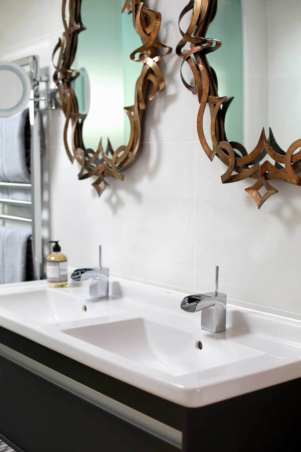 Double sink with stylish mirrors on wall. Photo credit: Alex Maguire