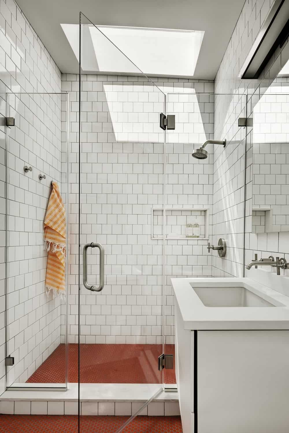 A close up look at this primary bathroom's shower room surrounded by tiles walls and red floors.