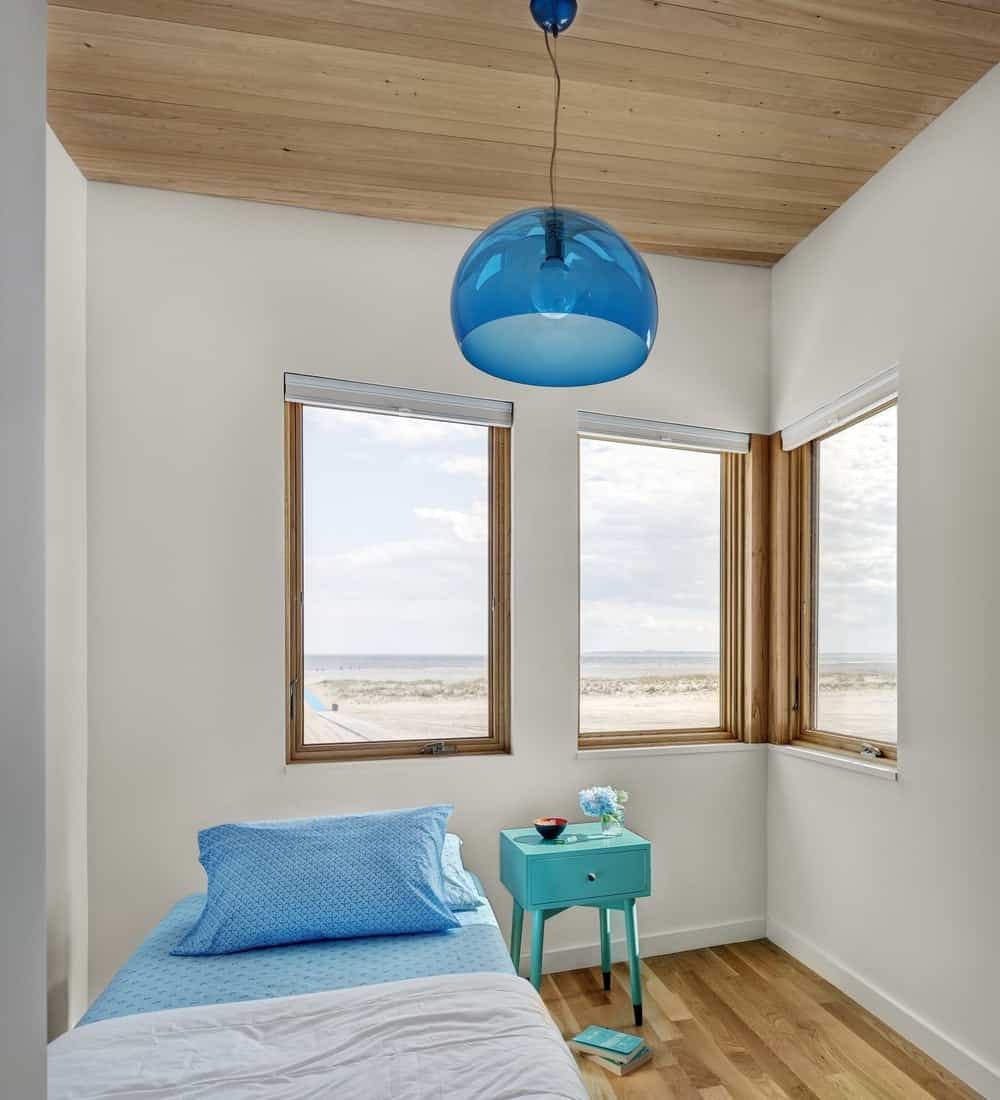 One of Surfboard house's bedroom with cool blue pendant lighting, single bed and glass windows. Photo credit: Francis Dzikowski/OTTO