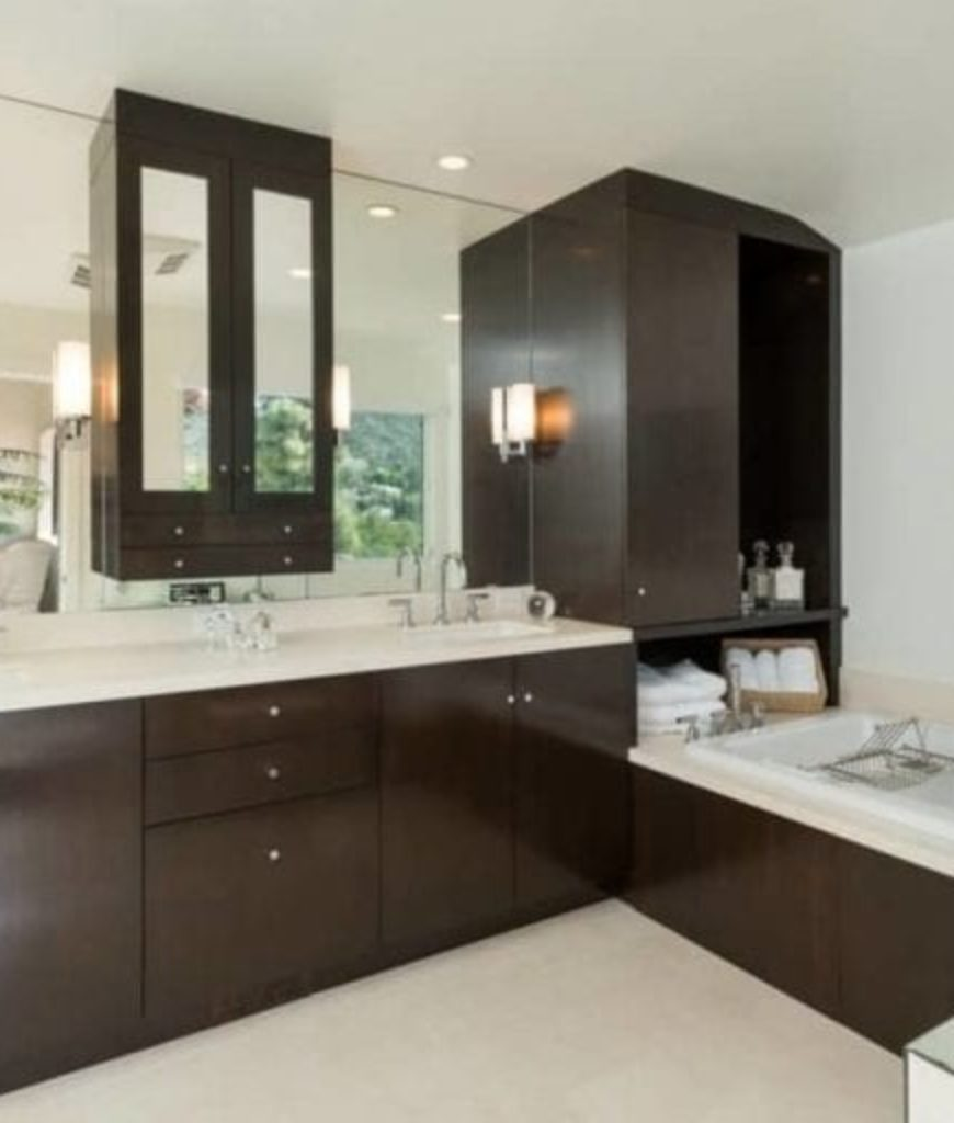 Another look of the bathroom featuring white walls and espresso-finish cabinets along with a corner tub.